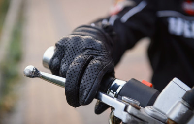 protective biker gloves on a motorcycle wheel. Driver decelerates, close-up